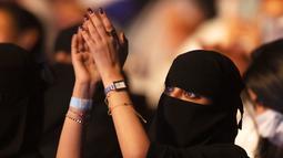 Seorang wanita yang telah divaksinasi virus corona bertepuk tangan saat menonton penyanyi Saudi Mohammed Abdu di Super Dome di Jeddah, Arab Saudi (8/7/2021). Konser ini diselenggarakan Otoritas Hiburan Umum Saudi. (AP Photo/Amr Nabil)