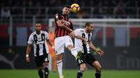 Penyerang muda AC Milan, Cutrone saat melakukan duel udara dengan Chiellini pada lanjutan laga serie a yang berlangsung di stadion San Siro, Milan (12/11). AC Milan kalah 0-2. (AFP/Marco Bertorello)