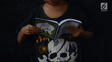 Seorang anak punk belajar mengaji dengan Iqro bersama Komunitas Tasawuf Underground di kolong flyover Tebet, Jakarta, Sabtu (8/12). Komunitas ini mengajak anak-anak punk dan anak jalanan kembali ke kehidupan yang baik. (Merdeka.com/Imam Buhori)