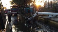 Genangan air di jalan Kaligawe dipompa dan dibuang ke saluran air di selatan jalan yang mati. (foto : liputan6.com / edhie prayitno ige)