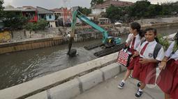 Sejumlah siswa SD berjalan di dekat pengerukan lumpur kali inspeksi Ciliwung, Jakarta, Selasa (3/3/2015). Pengerukan dilakukan untuk menjaga sungai tetap baik dan lancar. (Liputan6.com/Faizal Fanani)