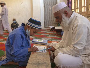 Seorang anak belajar Al-Quran selama bulan suci Ramadan di Jammu Kashmir Al Fallah Yateem Trust, Srinagar, India, Kamis (7/5/2020). Para ulama dan otoritas agama setempat mendesak warga untuk beribadah di rumah untuk mencegah penyebaran virus corona COVID-19. (AP Photo/Dar Yasin)