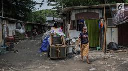 Warga berjalan di permukiman liar di kawasan Bypass, Pramuka, Jakarta Timur, Rabu (21/2). Rencana Pemprov DKI untuk membangun kantor pemadam kebakaran di lokasi tersebut terkendala oleh bangunan liar yang diduduki pemulung. (Liputan6.com/Faizal Fanani)