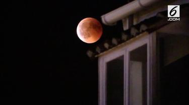 """Seorang kameraman merekam gerhana """"Blood Moon"""" terpanjang di abad ke langit malam Madrid, Spanyol, pada tanggal 27 Juli."""