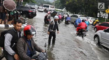 Sejumlah pengendara menerobos banjir yang merendam kawasan Gambir, Jakarta, Kamis (15/2). Banjir tersebut mengakibatkan jalan di sekitar lokasi terpaksa ditutup karena tidak bisa dilalui kendaraan bermotor. (Liputan6.com/Immanuel Antonius)