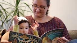 Yusuf Kamel (2) dibacakan buku ibunya, Nadia Chaouch  sambil menunggu buka puasa dirumahnya di Seattle (28/4/2020). Keluarga itu, seperti Muslim lainnya selama pandemi, melaksanakan bulan puasa Ramadan dengan doa dan refleksi dirumahnya daripada bertemu komunitas dan ke masjid. (AP/Elaine Thompson)