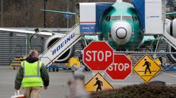 Pekerja Boeing berjalan ke arah  jet 737 Max di Renton, Washington, Senin (16/12/2019). Boeing Co mengumumkan akan menghentikan untuk sementara waktu produksi pesawat jenis 737 MAX – yang sudah dilarang terbang – pada Januari 2020 mendatang. (AP/Elaine Thompson)