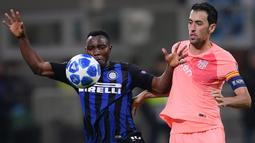 Gelandang Inter Milan, Kwadwo Asamoah, berebut bola dengan gelandang Barcelona, Sergio Busquets, pada laga Liga Champions di Stadion San Siro, Milan, Selasa (6/11). Kedua klub bermain imbang 1-1. (AFP/Marco Bertorello)
