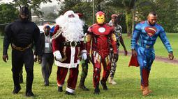 Sejumlah pria mengenakan kostum pahlawan super berjalan di istana kepresidenan di Pantai Gading (23/12). Mereka mengenakan kostum tokoh pahlawan super seperti Batman, Santa Claus, Iron Man dan Superman. (AFP Photo/Sia Kambou)