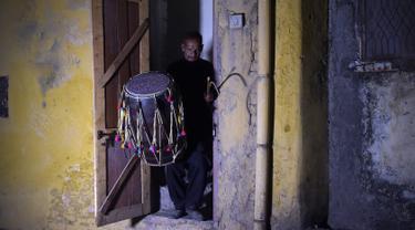 Seorang pria Pakistan Lal Hussain (66) membawa drumnya saat meninggalkan rumahnya untuk membangunkan warga untuk menyatap makanan saat sahur selama Ramadan di Rawalpindi (30/5). (AFP Photo/Aamir Qureshi)