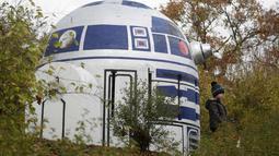 Seorang anak berada di dekat ventilasi bunker nuklir yang menyerupai robot R2-D2 film Star Wars di sebuah taman di Praha, Republik Ceko, (28/10). Kreatifitas seniman tersebut menghebohkan warga Praha. (AP Photo/Petr David Josek)