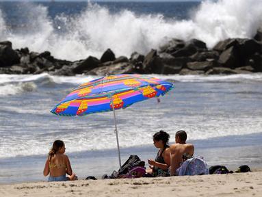 Para pengunjung duduk di Pantai Venice di Los Angeles (13/5/2020). Los Angeles County membuka kembali pantai-pantainya pada Rabu dalam pelonggaran terbaru pembatasan coronavirus yang telah menutup sebagian besar ruang publik dan bisnis California selama hampir dua bulan. (AP/Mark J. Terrill)