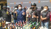 Tim Sancang Polres Garut yang dipimpin Kasat Narkoba AKP Maolana menunjukan ratusan miras berbagai ukuran dan merk hasil razia tim Sancang dari sebuah bungker penyimpanan di sekitar bilang Kerkof Garut. (Liputan6.com/Jayadi Supriadin)