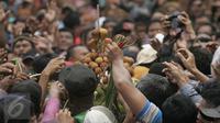 Ratusan warga berebut mendapatkan segala isi dari enam Gunungan Grebeg Mulud di halaman Masjid Agung, Surakarta, Kamis (24/12). Keluarnya gunungan menandai puncak acara Sekaten yang digelar untuk peringatan Maulid Nabi Muhammad. (Boy Harjanto)