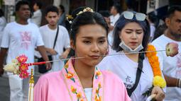 Seorang wanita menusuk pipinya dengan besi  saat mengikuti prosesi perayaan Festival Vegetarian tahunan di Phuket, Thailand, Kamis (3/10/2019). Festival dimulai pada malam pertama bulan lunar kesembilan dan berlangsung selama sembilan hari. (AFP Photo/Mladen Antonov)