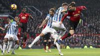 Bek Manchester United, Victor Lindelof, menyundul bola saat melawan Huddersfield pada laga Premier League di Stadion Old Trafford, Rabu (26/12). Manchester United menang 3-1 atas Huddersfield. (AP/Martin Rickett)