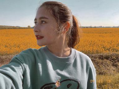 Cewek cantik yang lahir di Tangerang ini tampil cantik saat liburan ke London. Berpose dengan latar belakang padang bunga berwarna kuning, ia tampak memesona dengan rambut yang diikat ke belakang.  (Liputan6.com/IG/@prillylatuconsina96)