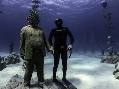 Penyelam bebas Angels Savvas berpose dengan patung di taman patung bawah laut MUSAM, Ayia Napa, Siprus, 18 September 2021. MUSAM disebut sebagai hutan bawah laut pertama di dunia. (EMILY IRVING-SWIFT/AFP)