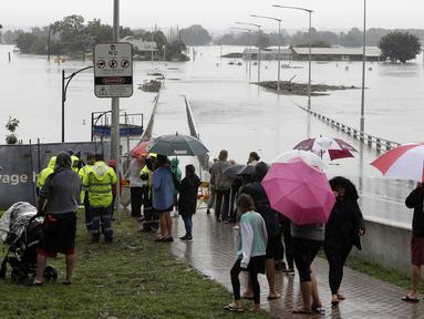 Warga menyaksikan banjir Sungai Hawkesbury di Windsor, barat laut Sydney, New South Wales, Australia (22/3/2021).  Negara bagian New South Wales yang padat penduduknya telah mengeluarkan lebih banyak perintah evakuasi menyusul banjir terburuk dalam beberapa dekade. (AP Photo/Rick Rycroft)