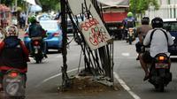 Pengendara melintas di sisi besi sisa pembangunan tiang Monorel di samping Stasiun Palmerah Jakarta, Selasa (15/12/2015). Sisa besi pembangunan tiang Monorel ini tampak tak terurus dan membahayakan pengguna jalan. (Liputan6.com/Helmi Fithriansyah)