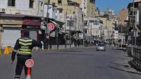 Seorang polisi memegang tanda berhenti di jalan yang hampir sepi di ibu kota Yordania, Amman, selama penguncian virus corona. [Khalil Mazraawi / AFP]