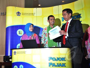 Presiden Joko Widodo (kanan) dibantu petugas mengisi surat pemberitahuan tahunan (SPT) pajak penghasilan menggunakan sistem e-filling di Kantor Pusat Ditjen Pajak Jakarta, Kamis (19/3/2015). (Liputan6.com/Faizal Fanani)