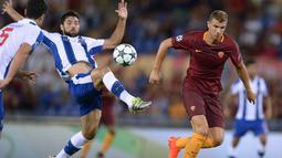 Pemain AS Roma, Edin Dzeko (kanan) berebut bola dengan pemain FC Porto Danilo pada leg 2 babak play off Liga Champions  di Olympic Stadium, Rome (24/8/2016) dini hari WIB. (AFP/Filippo Monteforte)