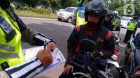 Polisi menilang pengendara sepeda motor saat razia di kawasan BSD, Tangerang Selatan, Banten, Kamis (23/1/2020). Polres Tangerang Selatan menggelar razia untuk meningkatkan tertib berlalu lintas, disiplin kendaraan, dan mempersempit gerak pelaku kejahatan jalanan. (merdeka.com/Arie Basuki)