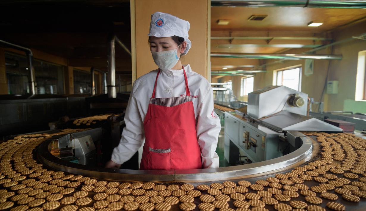 Seorang pekerja berdiri di depan mesin produksi kue merek Taeha di Pabrik Bahan Makanan Unha Taesong, Pyongyang, Korea Utara, 6 April 2021. (KIM Won Jin/AFP)