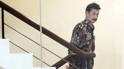 Bupati Solok Selatan Muzni Zakaria menaiki tangga bersiap menjalani pemeriksaan oleh penyidik di Gedung KPK, Jakarta, Jumat (21/06/2019). Muzni Zakaria diperiksa sebagai tersangka terkait kasus korupsi pengadaan barang dan jasa di Kabupaten Solok Selatan. (merdeka.com/Dwi Narwoko)