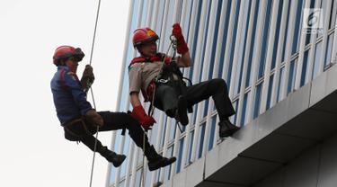 Kepala BNPB Willem Rampangilei (kanan) dievakuasi menggunakan tali dari lantai 10 saat simulasi bencana di Gedung Graha BNPB, Jakarta, Kamis (26/4). Simulasi dilakukan dalam rangka Hari Kesiapsiagaan Bencana Nasional. (Liputan6.com/Arya Manggala)