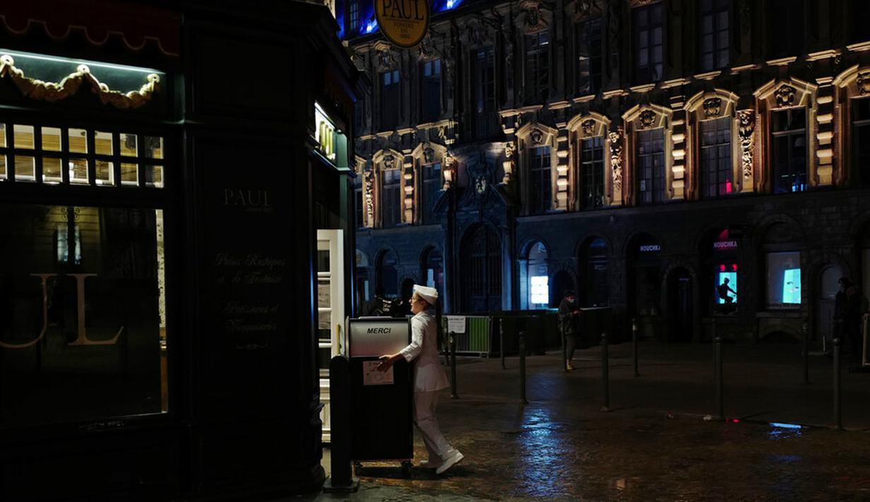 Seorang pelayan menutup teras bar di Lille, Prancis, Jumat (16/10/2020). Prancis mengerahkan 12.000 polisi untuk memberlakukan jam malam baru mulai Jumat malam hingga bulan depan untuk memperlambat penyebaran COVID-19. (AP Photo/Michel Spingler)