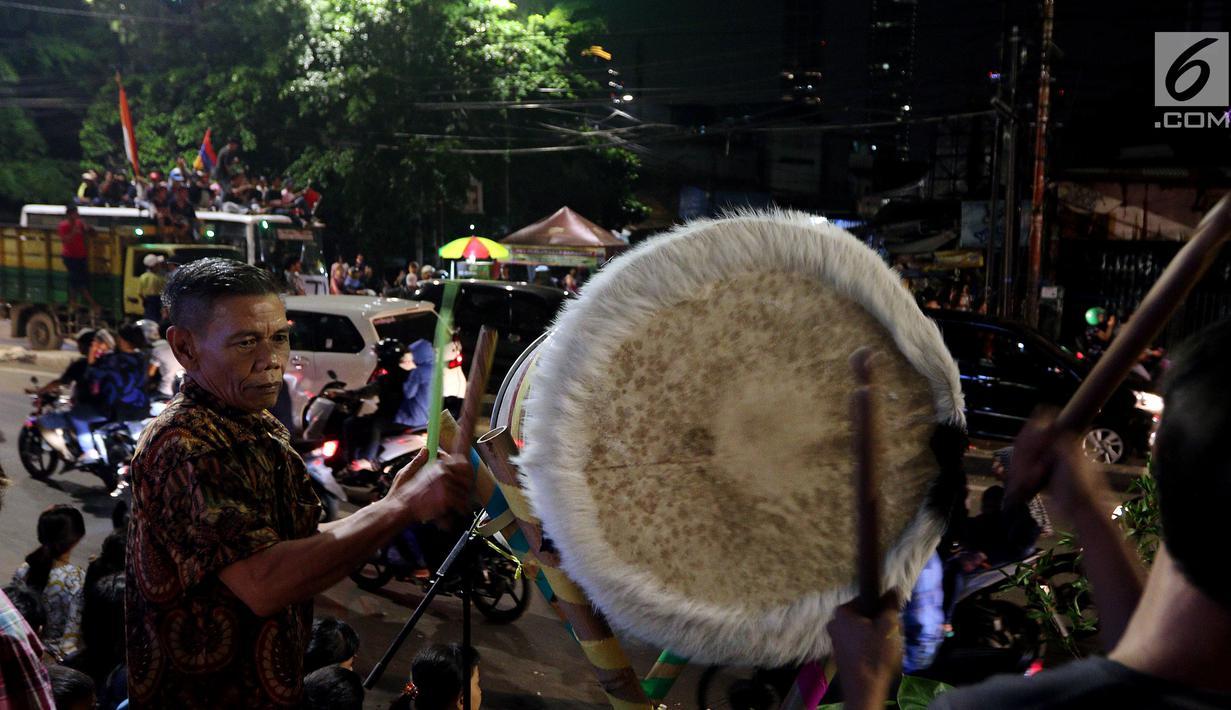 Warga menabuh beduk saat memeriahkan malam takbiran di sepanjang Jalan Mas Mansyur, Tanah Abang, Jakarta Pusat, Kamis (14/6) malam. Pemerintah menetapkan 1 Syawal 1439 Hijriah atau Idul Fitri jatuh pada Jumat (15/6) besok. (Liputan6.com/Johan Tallo)