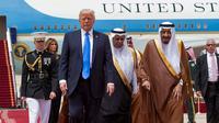 Donald Trump disambut Raja Salman saat tiba di Bandara Internasional Raja Khalid di Riyadh (20/5). Kunjungan ini akan membicarakan perjanjian politik dan perdagangan serta dukungan atas perang melawan para militan. (AFP/Saudi Royal Palace/Bandar Al-Jalou)