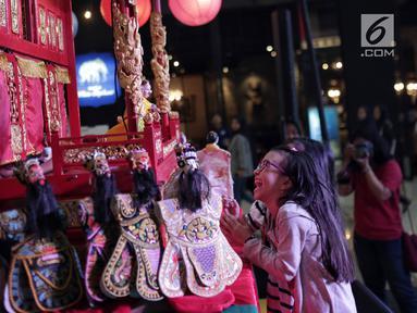 Pengunjung menyaksikan pementasan wayang potehi di salah satu mall di Jakarta, Jumat (1/2). Pementasan wayang potehi  tersebut diadakan dalam rangka menyambut Tahun Baru Imlek. (Liputan6.com/Faizal Fanani)