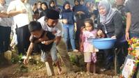 Ade Jigo dan kedua anaknya di pemakaman istrinya, Meyuza Zainal Abidin (Dok. Keluarga Ade Jigo / Nefri Inge)