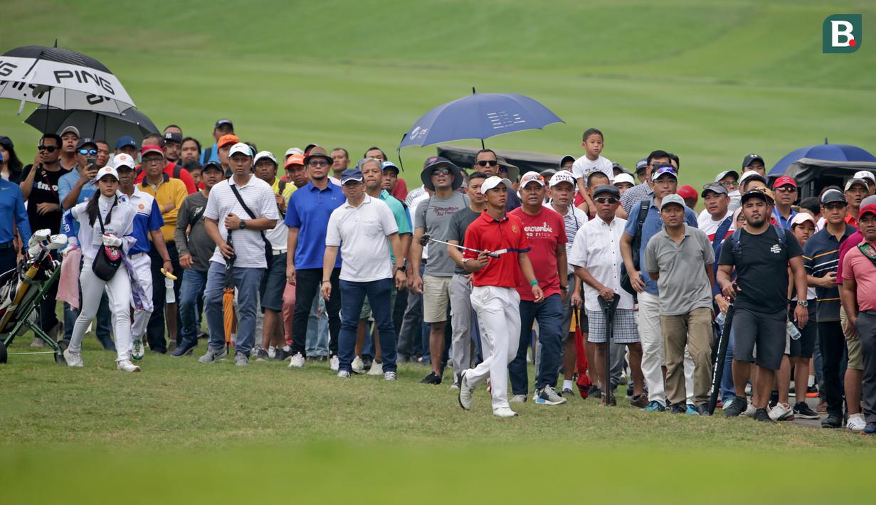Ratusan penonton dengan setia mengikuti aksi Naraajie Emerald Ramadhan Putra (tengah) pegolf amatir Indonesia berusia 19 tahun yang sempat memimpin perolehan skor di turnamen golf pro BRI Indonesia Open 2019, Minggu (1/9/2019). (Bola.com/Peksi Cahyo)