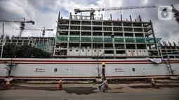 Pekerja melintas di depan proyek pembangunan rumah susun sewa (Rusunawa) PIK Pulogadung, Jakarta, Kamis (25/2/2021). Pemprov DKI Jakarta menargetkan proyek pembangunan 10 rusun rampung pada tahun 2021. (merdeka.com/Iqbal S. Nugroho)