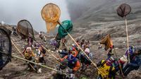 Sejumlah orang mencoba menangkap sajen yang dilemparkan ke kawah dalam ritual Yadnya Kasada di Gunung Bromo, Probolinggo, Jawa Timur, Kamis (18/7/2019). Ritual ini diselenggarakan berabad-abad silam saat manusia pertama kali mendiami kawasan kaki Gunung Bromo. (JUNI KRISWANTO/AFP)