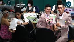 Pasangan sesama jenis Shane Lin dan Marc Yuan serta Cynical Chick dan Li Ying-Chien berpose di kantor pemerintahan Taipei, Taiwan, Jumat (24/5/2019). Ratusan pasangan sesama jenis di Taiwan bergegas ke kantor pemerintahan pada hari pertama pelegalan pernikahan sesama jenis. (Sam YEH/AFP)