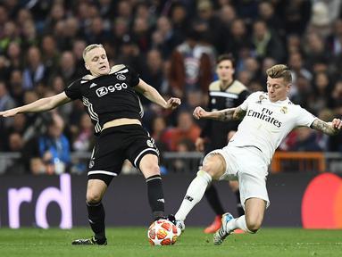 Gelandang Ajax, Donny van de Beek (kiri) berebut bola dengan gelandang Real Madrid, Donny van de Beek pada laga leg kedua babak 16 besar Liga Champions di stadion Santiago Bernabeu, Madrid pada 5 Maret 2019. Manchester United resmi memboyong van de Beek dari Ajax. (AFP/Gabriel Bouys)