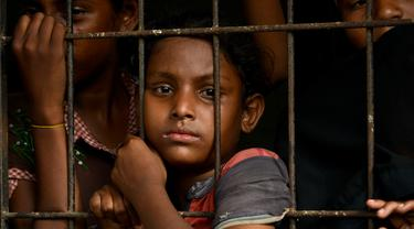 Anak-anak pengungsi Rohingya menunggu di pusat penampungan sementara bekas kantor Imigrasi Punteuet di Lhokseumawe, Aceh Utara (26/6/2020). Hampir 100 pencari suaka Rohingya yang terdampar di lepas pantai Aceh pada (25/6/2020) lalu. (AFP Photo/CHAIDEER MAHYUDDIN)