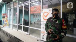 Tentara berdiri menjaga kotak hasil rekapitulasi penghitungan suara di TPS tingkat kelurahan di Kecamatan Pamulang, Tangerang Selatan, Banten, Kamis (10/12/2020). Proses rekapitulasi suara ditunda sementara karena terkendala jaringan ke server KPU Pusat down. (merdeka.com/Dwi Narwoko)