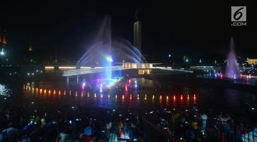 Warga menonton pertunjukan air mancur menari di Lapangan Banteng, Jakarta, Sabtu (11/8). Pertunjukan air mancur di Lapangan Banteng diputar setiap 15 menit sekali. (Merdeka.com/Imam Buhori)