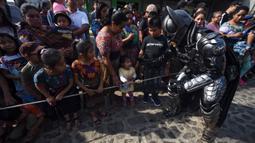 Anggota Saturno Club mengenakan kostum Batman menyapa anak-anak selama parade Dance of Costumes tahunan di sepanjang jalan kota Sumpango, Guatemala, Senin (30/12/2019). Parade kostum yang menampilkan karakter televisi dan film ini untuk memeriahkan malam pergantian tahun. (ORLANDO ESTRADA/AFP)