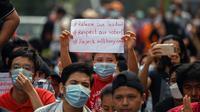 Seorang demonstran muda memegang poster saat ikut serta dalam demonstrasi menentang kudeta militer di Yangon, Myanmar pada Sabtu (6/2/2021). Ini adalah demonstrasi besar pertama sejak para jenderal merebut kekuasaan. (YE AUNG THU / AFP)