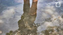 Refleksi bayangan Amir saat memancing di genangan air yang membanjiri TPU Semper, Jakarta, Selasa (2/2/2021). Biasanya warga ramai datang memancing tiap pagi dan sore hari, bahkan hingga malam. (merdeka.com/Iqbal S. Nugroho)