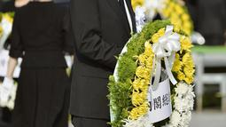 Perdana Menteri Jepang Shinzo Abe membawa karangan bunga pada saat upacara peringatan 70 tahun jatuhnya bom atom di Hiroshima, Jepang (6/8/2015). 140.000 penduduk Jepang tewas akibat Bom Atom. (REUTERS/Kyodo)