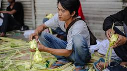 Pedagang menata kulit ketupat dagangannya di sebuah pasar kawasan Ciracas, Jakarta, Kamis (16/7/2015). Menjelang Lebaran, warga mulai ramai membeli kulit ketupat. (Liputan6.com/Faizal Fanani)