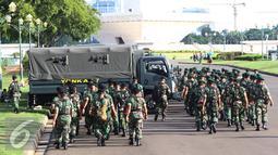 Petugas TNI bersiap untuk mengikuti apel gabungan di Monas, Jakarta, Kamis (31/12). Sebanyak 1300 personel gabungan yang terdiri dari polisi, TNI, Pol PP, dan Pramuka dikerahkan untuk mengamankan perayaan malam tahun baru. (Liputan6.com/Immanuel Antonius)